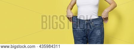 The Concept Of Diet, Proper Nutrition, Weight Loss. Slim Woman Showing Loose Jeans And Her Loss Weig