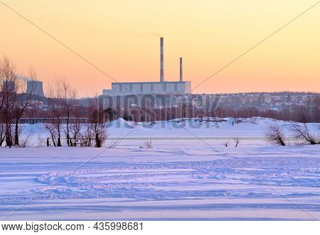 Winter Morning On The Ob. Frozen Snowy River Bank, Heat Station Pipes On The Horizon In Novosibirsk