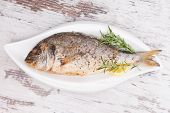 Delicious grilled sea bream fish on white plate with lemon and rosemary on white wooden background top view. Culinary mediterranean seafood eating. poster
