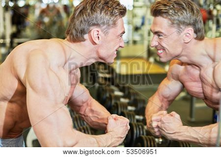 Grinning bodybuilder poses in gym hall demonstrating muscles in front of mirror poster