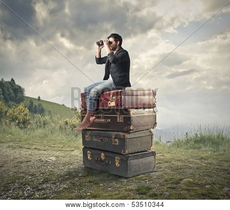 young man sitting on a pile of vintage suitcases looking with binoculars the panorama