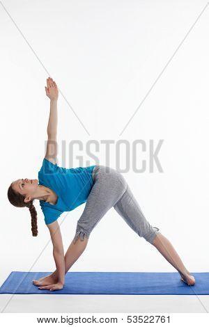 Yoga - young beautiful woman  yoga instructor doing Revolved Triangle asana pose (Parivrtta Trikonasana) exercise isolated on white background
