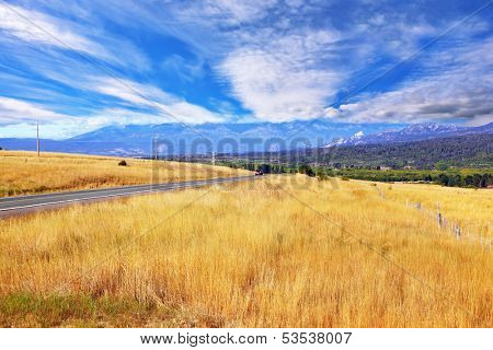 Picturesque field after harvesting at sunset. A field of yellow grass demarcated green alleys. See the mountains on the horizon, and cumulus clouds