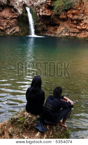 Two persons one female and one male watching a beautiful waterfall. poster