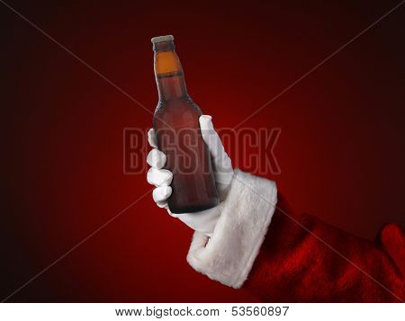 Closeup of Santa Claus holding a bottle of beer. Only hand and arm are visible. Horizontal format on a light to dark red spot background.