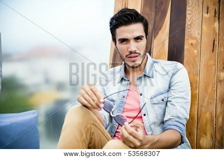 Handsome young man sitting outdoors, looking at the camera with a serious expression
