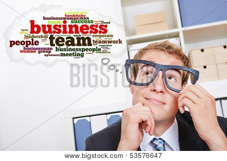 Business man with tag cloud thinking about teamwork in the office