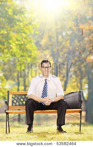 Smiling young businessman sitting on a wooden bench and looking at camera in a park on a sunny day