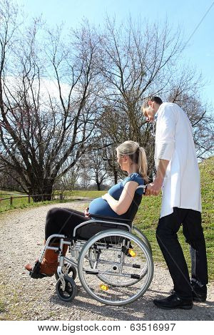 Pregnant Woman In Wheelchair With Doctor