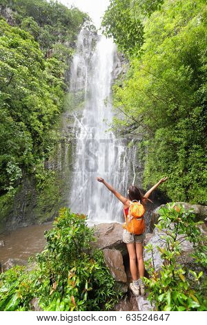 Happy hiker - Hawaii tourists hiking by waterfall. Woman cheering during travel on the road to Hana on Maui, Hawaii. Ecotourism concept image with happy female hiker.
