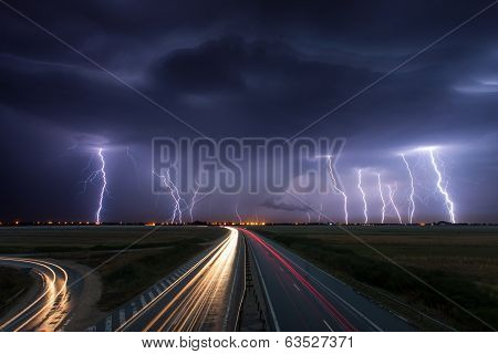Thunderstorm And Lightnings In Night Over A Highway With Car Lightning