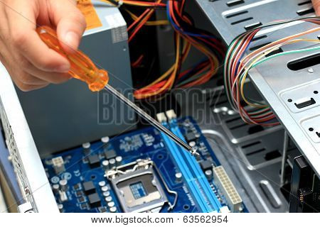 Close-up Of Technician's Hand Assembling Personal Computer