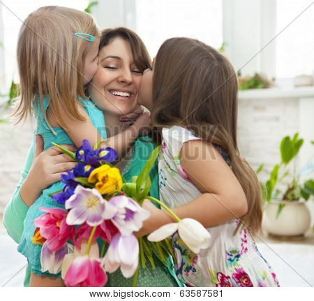 Happy Woman And Her Little Daughters In The Living Room