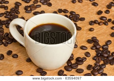 Cup Of Black Coffee And Coffee Beans On Wooden Background.