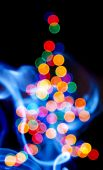 Defocused Christmas tree and the blue smoke poster