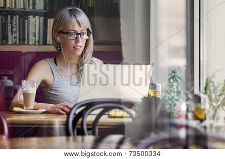 Woman working with computer in cafe