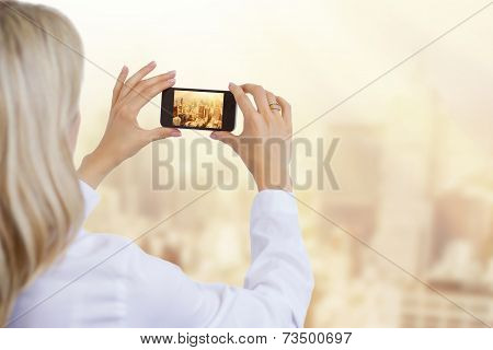 Woman taking photo of city in morning light