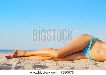 Beautiful women's legs on the beach