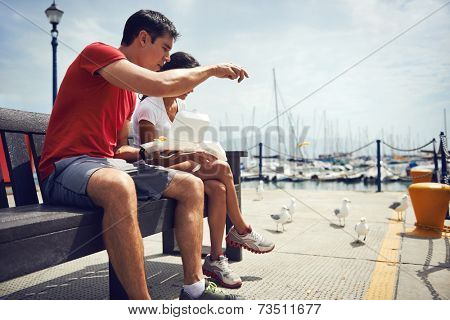 A young couple in fitness clothing eating take away fish and chips by the harbour with seagulls beside them