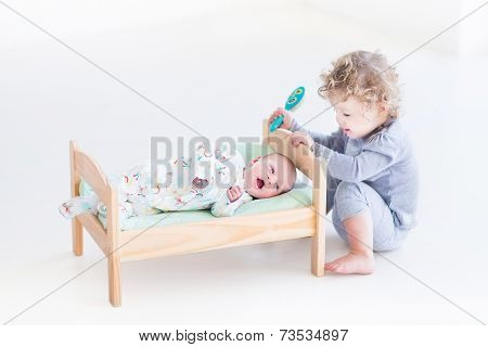 Funny Curly Toddler Girl Playing With Hew Newborn Baby Brother In A Toy Bed Trying To Brush His Hair