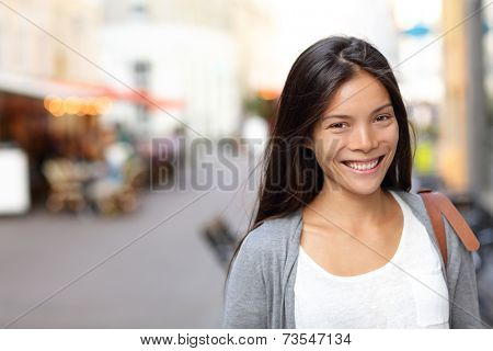 Asian woman candid portrait from street in Copenhagen city, Denmark. Young urban female smiling looking at camera. poster