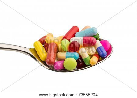 many colorful pills on a spoon. symbol photo for tablets addiction and abuse of drugs.