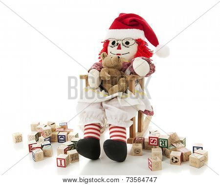 A happy rag doll rocking her toy bear.  They're surrounded by scattered alphabet blocks.  On a white background.