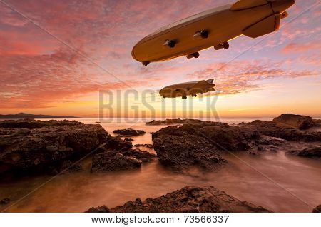 Two Zeppelins gliding above a rocky coast in vibrant sunset