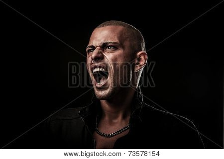 Handsome Young Man Screams Into A Dark Copy Space As A Sign Of Freedom Of Speach
