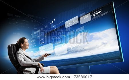 Young businesswoman in chair near tv screen with click