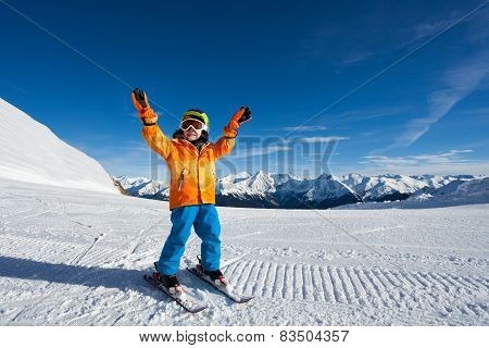 Happy boy with arms up and ski mask on ski-track