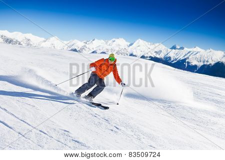 Skier in mask slides fast while skiing from slope