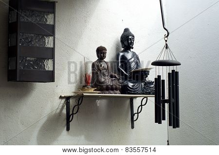 Two Buddhas On Shelf With Incense And Windchime