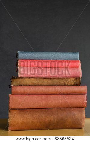 Books Stacked On Classroom Desk With Chalkboard Background