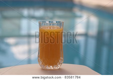 orange juice glass in front of pool