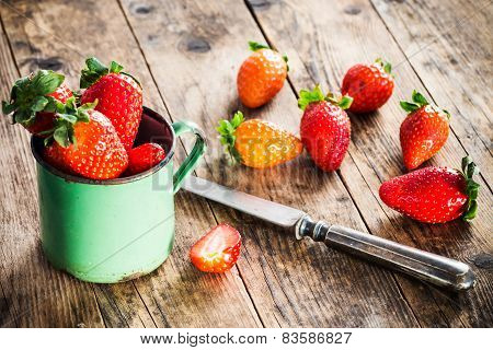 Strawberry Scattered Around The Old Wooden Table.