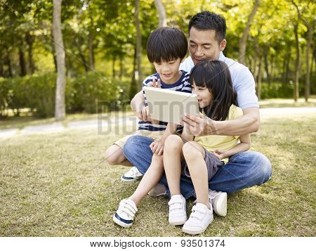 Asian Father And Children Using Tablet Outdoors