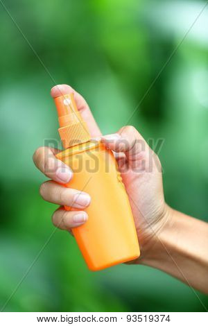 Mosquito repellent. Woman spraying insect repellent for skin outdoor in nature forest using spray bottle.