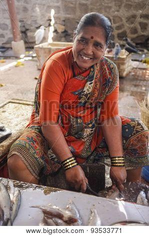 MUMBAI, INDIA - 11 JANUARY 2015: Woman cleaning fish on a fishmarket.