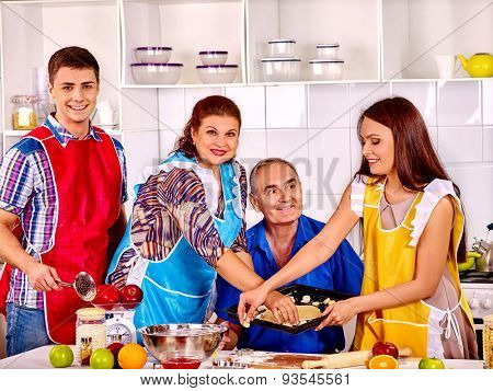 Happy senior family with adult children cooking at kitchen. Two generations.