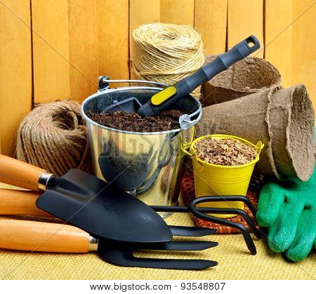 Gardening Tools, Peat Cups, Thread; Seeds In Tins Against Wooden Fence