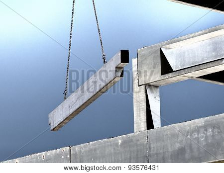 Crane lifting concrete truss for installing in building skeleton poster