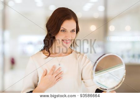 sale, consumerism, shopping and people concept - happy woman choosing and trying on pendant at jewelry store