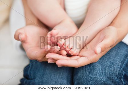 Close-up Of A Young Mother Sitting On The Sofa With Her Baby
