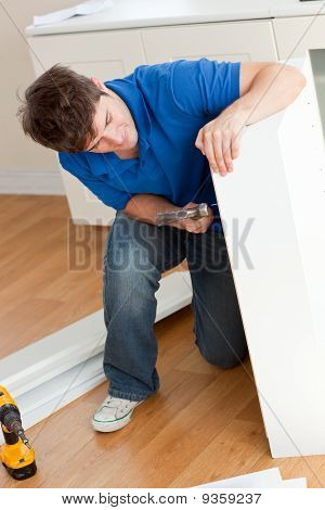 Good-looking Man Assembling Furniture And Holding A Hammer