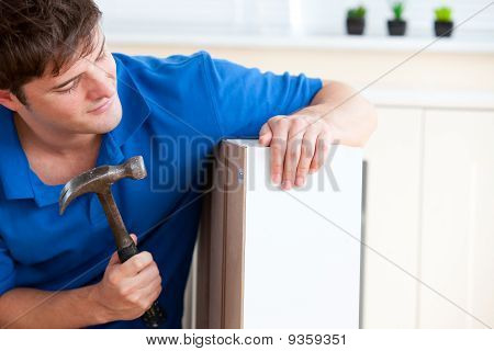 Young Man Building Furniture Using A Hammer And A Nail