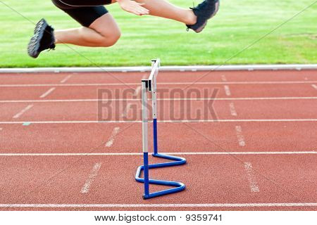 Assertive Male Athlete Jumping Above Hedge During A Race