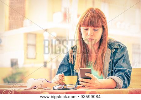 Vintage Filtered Portrait Of Serious Pensive Young Woman With Smartphone - Hipster Girl Using Phone