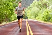 Sport and fitness runner man running on road training for marathon run doing high intensity interval training sprint workout outdoors in summer. Male athlete sports model fit and healthy aspirations. poster