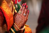 Folder hands of a traditional Indian bride in wedding attire praying during her wedding. poster